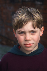 Portrait of young boy standing outside looking serious,
