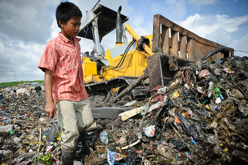 Taupik, 14, working alongside a bulldozer on the 'Trash mountain', Makassar, Sulawesi, Indonesia.  Many of the pickers follow the bulldozers as they move newly dumped waste, uncovering plastic and metal for recycling in the process.