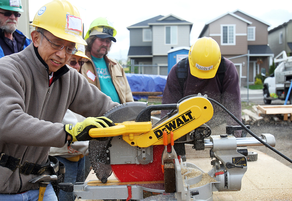 Volunteer Yee Lee runs a saw on the worksite...John Gray was born 92 years ago and grew up poor in rural Oregon. He made a fortune in the chainsaw industry after World War II, and now he has donated more than a million dollars to Habitat for Humanity to buy land in Portland for low-income housing. Volunteers work to build solid foundations on the largest of these land parcels on Wednesday, May 2, 2012.