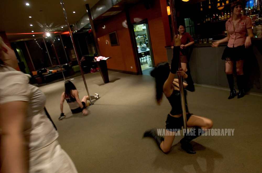 "MELBOURNE, AUSTRALIA - AUGUST 10: Students practice their moves at a beginners pole-dancing class at the Imperial Hotel, August 10, 2006, Melbourne, Australia. Previously reserved for strip clubs, pole dancing is now quickly becoming a new fitness crazy throughout Australia, Europe and the US with thousands of women from all walks of life leaving traditional gymnasiums for the more social and challenging art of pole dancing. Pole dancing for fitness exploded onto the public scene after celebrities such as Angelina Jolie, Jennifer Anniston and Britney Spears professed it was their favourite form of exercise. Classes are often small in numbers giving a more personal atmosphere and strong bonds of friendship are often formed between students and instructors. Instructors claim a noticeable increase in their students' self-confidence after only a few weeks. Most students claim even thought it's a rigorous workout, they're having so much fun it doesn't feel like exercise at all. According to ""Polestars"", a British company that began setting up classes throughout six Australian cities in 2004,  ""a good session on the pole"" can burn more calories than at the gym and provide more muscle tone.  (Photo by Warrick Page)"