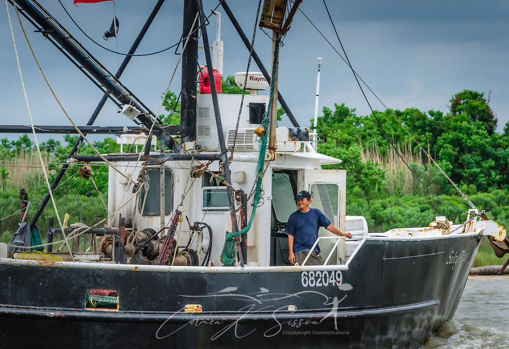 "A deckhand smiles aboard the Salty Pirate as he heads back to dock following a long day of shrimping in Bayou La Batre, Alabama, May 16, 2015. Bayou La Batre is known as the ""Seafood Capital of Alabama."" (Photo by Carmen K. Sisson/Cloudybright)"