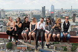 © Licensed to London News Pictures. 21/08/2018. London, UK. Guests eat KFC fried chicken taking part in recreating one of the most iconic images on the 20th century; Lunch Atop a Skyscraper. Deliveroo invited lucky guests to sit on the steel girder and dine 450ft in the air suspended with a panoramic view of London enjoying the companies menu.  Photo credit: Ray Tang/LNP