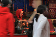 Woman serving food at the twice-weekly Turkish market on Maybachufer beside the Landwehrkanal, Berlin, Germany. Picture by Manuel Cohen