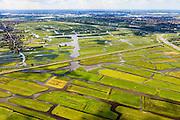 Nederland, Noord-Holland, Gemeente Oostzaan, 14-06-2012; polder Oostzaan, doorsneden door de spoorlijn Zaandam - Purmerend. Rechts autosnelweg A6 en Zaandam, links het lintdorp Oostzaan. De verkaveling in het gebied is het resultaat van veenontginning. .Polder and village Oostzaan, north of Amsterdam (at the horizon). The division in plots in the area is the result of peat extraction..luchtfoto (toeslag), aerial photo (additional fee required);.copyright foto/photo Siebe Swart