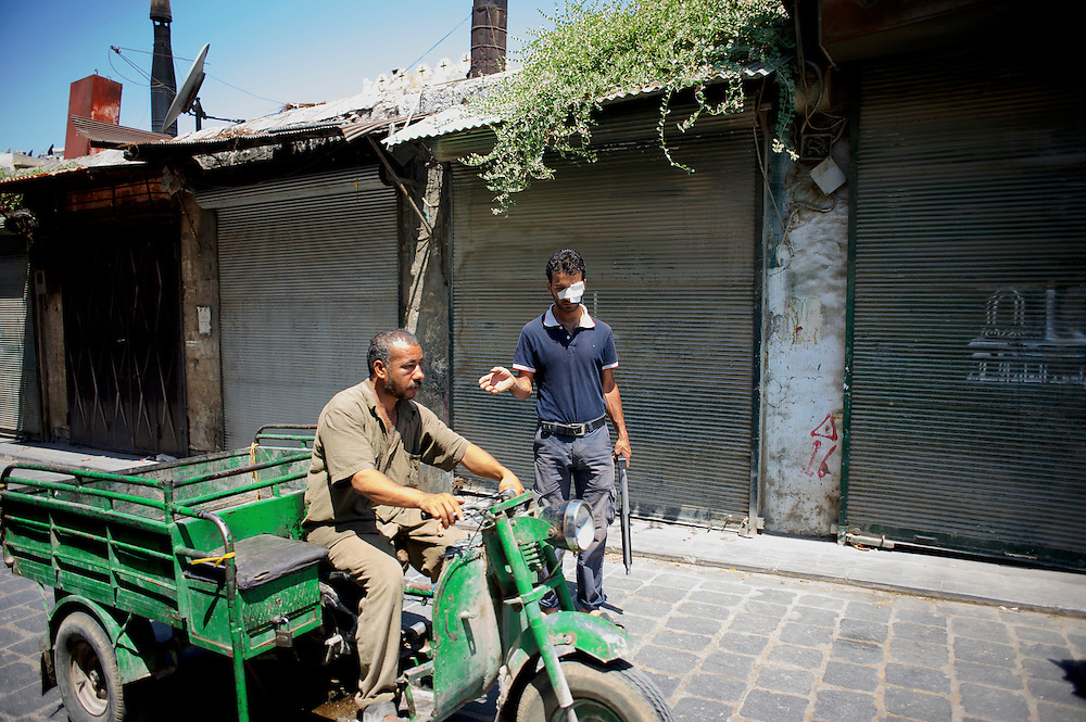 August 14, 2012 - Aleppo, Syria: A Free Syria Army fighter orders a local resident to proceed in a rebel checkpoint in Babal Nassar neighborhood in Aleppo's old city. The Syrian Army have in the past ten days increased their attacks on residential neighborhoods where Free Syria Army rebel fights have their positions in Syria's commercial capital, Aleppo.
