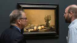 "© Licensed to London News Pictures. 01/07/2016. London, UK.  A Sotheby's staff member discusses ""Still Life of lemons and olives, pewter plates, a roemer and facon de venies wine glass on a ledge"" by Pieter Claesz (est. GBP 1.8-2.5 million), with a potential buyer at the preview of Sotheby's London Old Masters evening sale which takes place 6 July.   Photo credit : Stephen Chung/LNP"