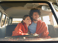 Couple wrapped in blanket in front seat of van view through windscreen