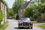 Motorist driving 1961 British made Alvis TD21 Series 1 drophead ooupe classic car Asthall village, The Cotswolds England