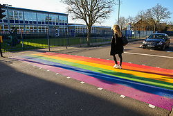 © Licensed to London News Pictures. 11/02/2020. London, UK. A woman crosses at a LGBT rainbow-coloured crossing outside a school in north London, which is installed in celebration of LGBT History Month. The school, which is the first one in England to have a rainbow coloured crossing outside a school, claims that it has received around 200 abusive messages on social media. Photo credit: Dinendra Haria/LNP