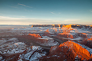 The sun rises over the Colorado River and illuminates the sides of the sandstone cliffs. Dead Horse Point State Park, Utah