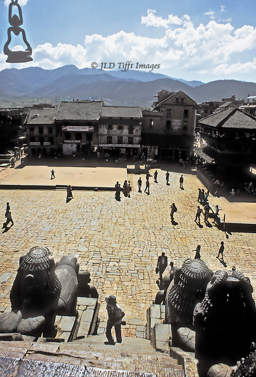 Bhaktapur main square from the top of the Nayatapola Temple.  Visitors dot the pavement, one beginning to climb the temple stairs. Mountain landscape beyond to the south of the square.  High noon, direct sunlight.