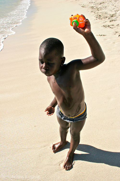 A boy is posing with toy camera in one beach of Saint martin in the Netherlands Antilles.