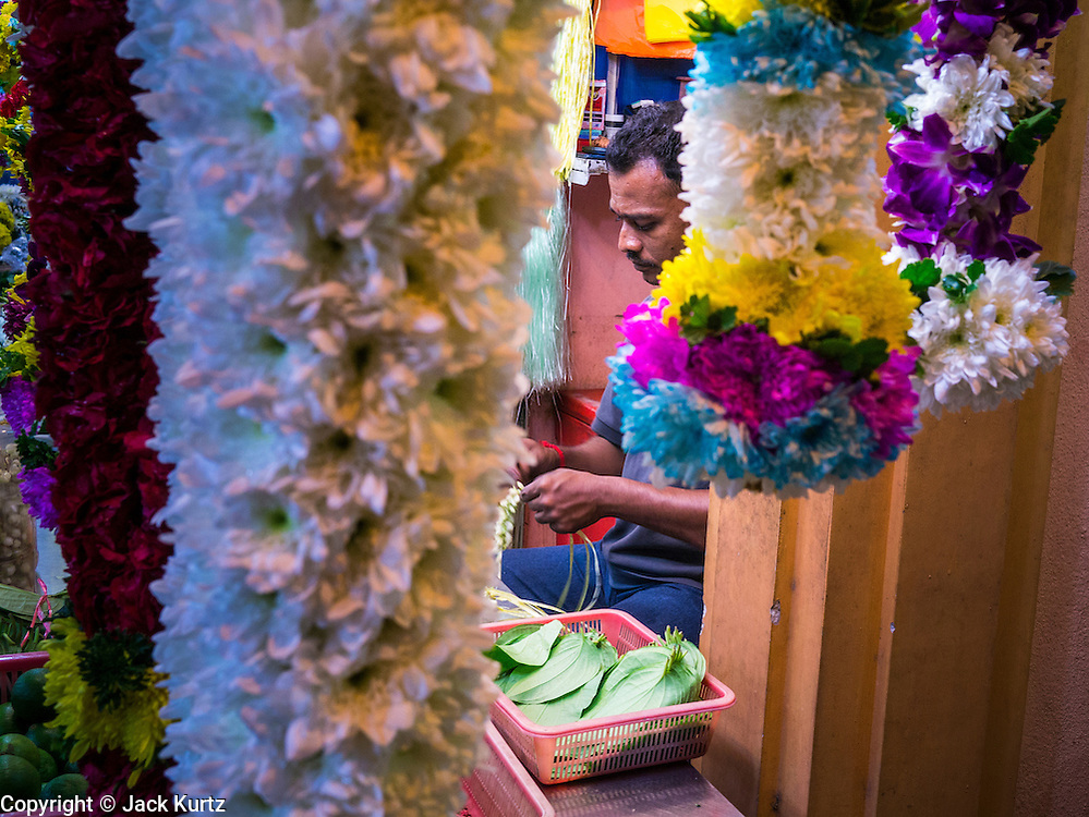 "20 DECEMBER 2012 - KUALA LUMPUR, MALAYSIA: Flower garland sellers near a Hindu shrine on Jalan Tun Sambanthan, the main street in ""Brickfields,"" the Little India section of Kuala Lumpur, Malaysia. The ""Little India"" section of Kuala Lumpur is also known as ""Brickfields."" The area has recently been renovated and has emerged as a tourist draw. It's within walking distance of KL Stesen Sentral, the Kuala Lumpur central train station.    PHOTO BY JACK KURTZ"