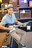 Portrait of happy customer playing electric guitar in music store
