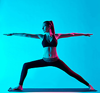 one caucasian woman exercising Virabhadrasana warrior position  yoga exercices  in silhouette studio isolated on blue background