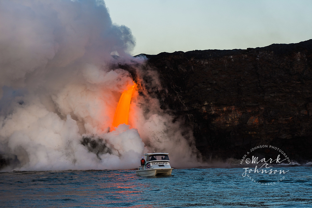 Tour boat watching the spectacular lava flow into the ocean at Kamokuna, Big Island, Hawaii