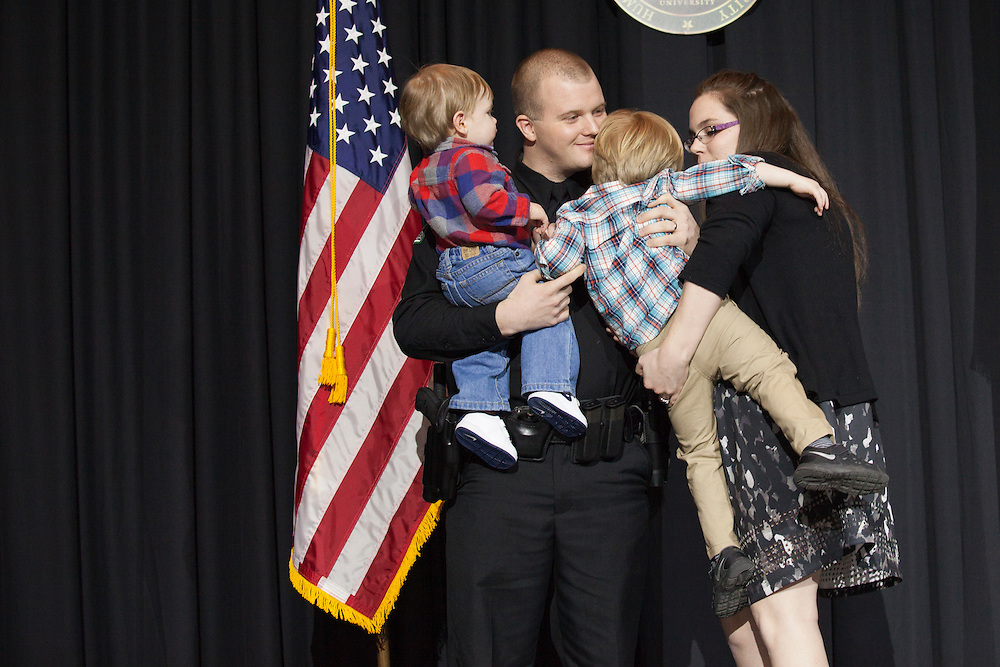 Officer Harlow and his family on stage after his new badge was pinned on him by his wife at the Badge Pinning and Employee Recognition Ceremony on Monday, February 8, 2016. Photo by Kaitlin Owens