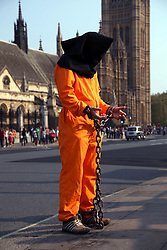 21 April 2011. London, England..A Guantanamo Bay protester stands outside  the Houses of Parliament, part of the Royal wedding route the procession will pass en route to Buckingham Palace in the run up to Catherine Middleton's marriage to Prince William. The police have threatened to remove protestors from Parliament Square before the big day..Photo; Charlie Varley.