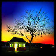 Oyster Bay, NY, March 17, 2015:  The sun sets at Theodore Roosevelt Memorial Park in Oyster Bay, Long Island. An empty, but illuminated booth at the park's entrance is juxtaposed against a brilliant sunset.         © Audrey C. Tiernan