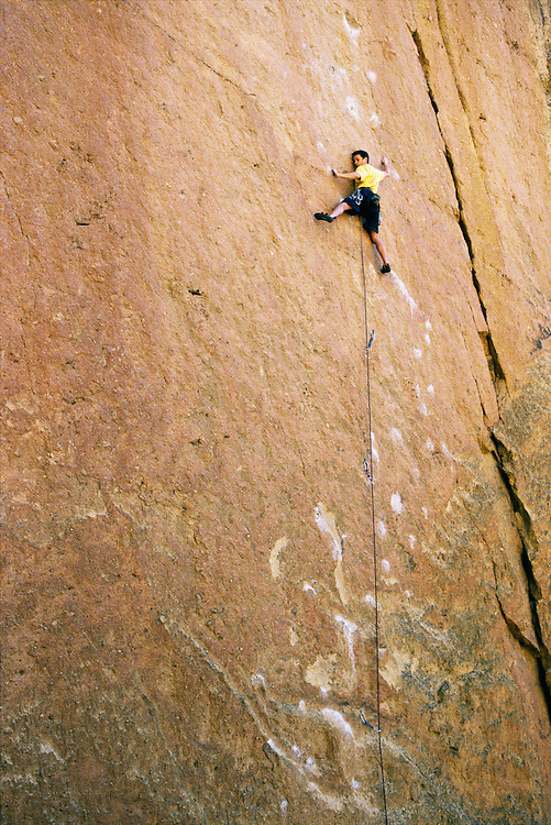 A male rock climber clinging to the side of a rock cliff<br />