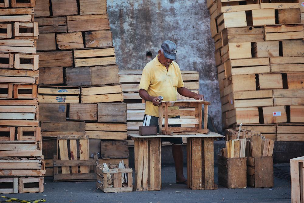 A man assembles crates for fruit and veg at Rio de Janeiro's CADEG Market.