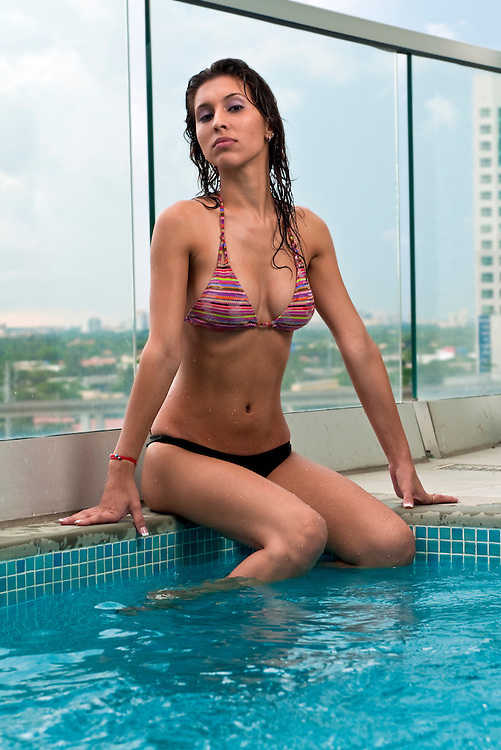 Young hispanic woman enjoys the spa in the terrace of a upscale building.