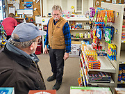 """25 FEBRUARY 2020 - BUTTERFIELD, MINNESOTA: MARK WARNER (center) owner of the True Value Hardware Store in Butterfield, MN, talks to a shopper in the grocery section. Butterfield is a farming community of about 500 people 130 miles southwest of the Twin Cities. The town has been a """"food desert"""" for 10 years after its only grocery store closed in 2010. Barb Mathistad Warner and Mark Warner purchased the True Value store in Butterfield in December, 2018 and started selling groceries in the store in May, 2019. For residents of Butterfield going to a grocery store meant driving 10 miles to St. James, MN, or 20 miles to Windom, MN, the two nearest communities with grocery stores. The USDA defines rural food deserts as having at least 500 people in a census tract living 10 miles from a large grocery store or supermarket. There is a convenience store in Butterfield, but it sells mostly heavily processed, unhealthy snack foods that are high in fat, sugar, and salt.   PHOTO BY JACK KURTZ"""