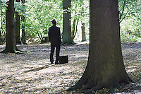 Business man standing with briefcase in middle of forest
