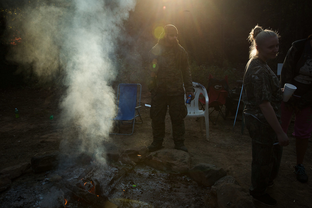 Militia members from the several states, all of whom identify as part of the III% movement, gather near Jackson, Ga. on Saturday, Oct. 29, 2016 for training exercises. Here, Chad LeGere, center, who goes by Killzone and is a member of the Georgia Security Force III% stands around the campfire while waiting for training exercises. Photo by Kevin D. Liles for The New York Times