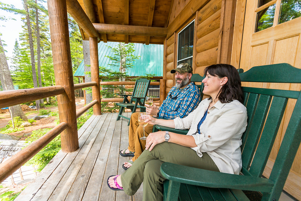 A couple enjoys a glass of wine on the front porch of their cabin at the Appalachian Mountain Club's Gorman Chairback Lodge.