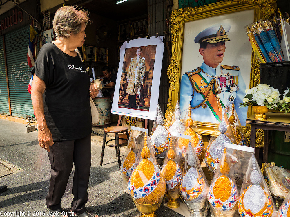 18 OCTOBER 2016 - BANGKOK, THAILAND: A woman wearing black mourning clothes walks past portraits of the late Bhumibol Adulyadej, the King of Thailand, and his son HRH Crown Prince Maha Vajiralongkorn. Crown Prince Vajiralongkorn is the heir apparent and will be coronated following his father's cremation. King Bhumibol Adulyadej died Oct. 13, 2016. He was 88. His death came after a period of failing health. Bhumibol Adulyadej was born in Cambridge, MA, on 5 December 1927. He was the ninth monarch of Thailand from the Chakri Dynasty and is also known as Rama IX. He became King on June 9, 1946 and served as King of Thailand for 70 years, 126 days. He was, at the time of his death, the world's longest-serving head of state and the longest-reigning monarch in Thai history.     PHOTO BY JACK KURTZ