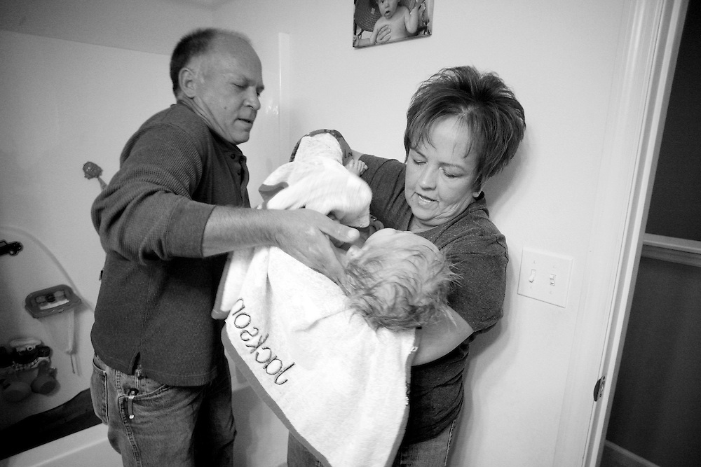 "Grandfather Frank lifts Kade from a bath into Fawn's arms being careful to support his neck. His four grandparents trade off caring for him during the day. ""If we didn't have both sets of grandparents to help, one of us would have had to quit our job,"" says Kade's father Josh."