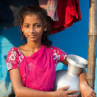 Rani Basfur, age 13 with a pot of water outside her house.<br />