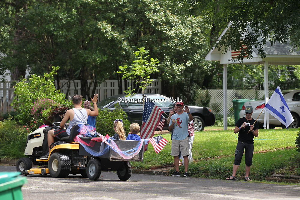Neighbors stand at the burb and greet the parade as it makes its way arounf the neighborhood.