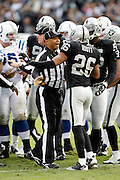 An NFL official calms down Oakland Raiders cornerback Stanford Routt (26) during a brief scuffle during the NFL week 16 football game against the Indianapolis Colts on Sunday, December 26, 2010 in Oakland, California. The Colts won the game 31-26. (©Paul Anthony Spinelli)
