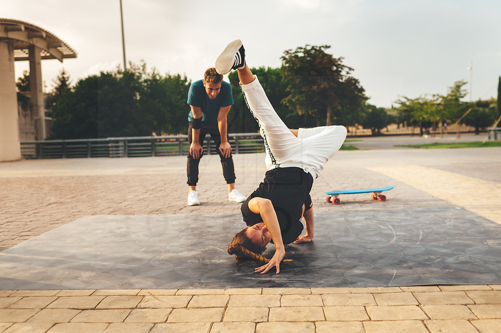 Group of young break dancers training in the street at sunset