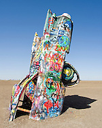Cadillac Ranch is a public art installation and sculpture in Amarillo, Texas, U.S. It was created in 1974 by Chip Lord, Hudson Marquez and Doug Michels, who were a part of the art group Ant Farm. It consists of what were (when originally installed during 1974) either older running used or junk Cadillac automobiles, representing a number of evolutions of the car line (most notably the birth and death of the defining feature of mid twentieth century Cadillacs; the tailfins) from 1949 to 1963, half-buried nose-first in the ground, at an angle corresponding to that of the Great Pyramid of Giza in Egypt.