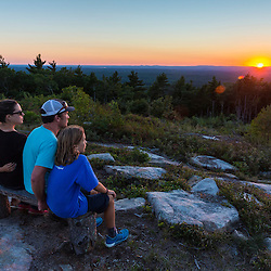 A family of four enjoying the sunset from the summit of Mount Agamenticus in York, Maine.