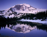 The Willis Wall of Mount Rainier's 14,411¬?ft (4,392¬?m) North Face reflected in alpine tarn at Mystic Pass, Mount Rainier National park Washington USA