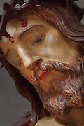 Detail of the head of a statue of Christ wearing the crown of thorns, in Saint Volusian Abbey, or the Abbatiale Saint-Volusien, in Foix, Ariege, Midi-Pyrenees, France. The original abbey church was built in the 12th century, but was later destroyed and rebuilt in the 17th century. The abbey houses the relics of St Volusian, 7th bishop of Tours, who died c. 495 AD, and its buildings now house the Prefecture of the Ariege. Picture by Manuel Cohen