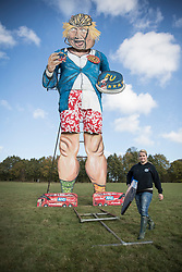 © Licensed to London News Pictures. 31/10/2018. Edenbridge, UK. Artist Andrea Deans walks past an effigy of former foreign secretary Boris Johnson as it is unveiled in Edenbridge, Kent ahead of its burning at the town's bonfire this Saturday. The 10 meter high figure stands over two EU referendum buses and Boris is also carrying an EU cake. Photo credit: Peter Macdiarmid/LNP
