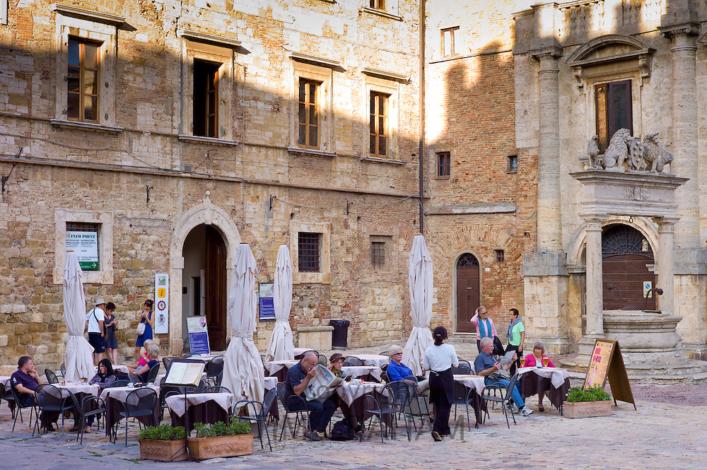 Diners eat al fresco at restaurant and bar by Palazzo del Capitano del Popolo, in Piazza Grande in Montepulciano, Tuscany, Italy RESERVED USE - NOT FOR DOWNLOAD - FOR USE CONTACT TIM GRAHAM