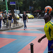 A street performer shows his football skills in front of traffic and passers by on the main street on Ipanema, Rio de Janeiro,  Brazil. 28th July 2010. Photo Tim Clayton..