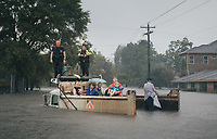 Rescue workers and civilians wait for emergency crews in a flooded dump truck in the Meyerland area of Houston, which received an unprecedented 50 inches of rainfall. Decades of rapid growth in Houston have spread concrete and asphalt over much of the city's more than 600 square miles. New development replaced floodplains, exacerbating drainage problems in a city that already tends to flood.