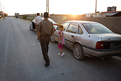 © Licensed to London News Pictures. 27/07/2014. Hamdaniyah, Iraq. Dilar Minowar Salim (9), an Iraqi Christian refugee from Mosul, looks back as she leaves a service held at a church in Hamdaniyah, Iraq.<br /> <br /> Having taken over Mosul Iraq's second largest city in June 2014, fighter of the Islamic State (formerly known as ISIS) have systematically expelled the cities Christian population. Despite having been present in the city for more than 1600 years, Christians in the city were given just days to either convert to Islam, pay a tax for being Christian or leave; many of those that left were also robbed at gunpoint as they passed through ISIS checkpoints. Photo credit: Matt Cetti-Roberts/LNP