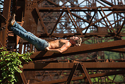 shirtless man resting on a train trestle