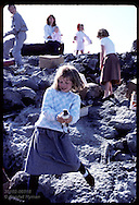 Eva Valsdottir, 9, walks down shore embankment to release puffin chick to sea on Heimaey Iceland