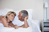 Affectionate couple looking in each others eyes lying in bed