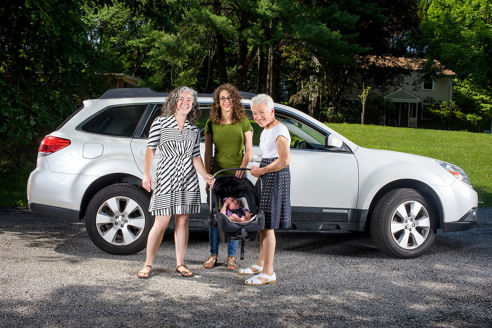 Pikesville, Maryland - June 25, 2015:  The Car Seat Ladies (L-R) Alisa Baer, 35, Emily Levine, 34, both from Manhattan, and Alisa's mother Deborah Baer, 67, from Pikesville, Maryland, hold Alisa's 7 week-old niece Leora Aghion in a Nuna Pipa infant car seat, ($300) at her sister's house in Pikesville, Maryland Thursday June 25th, 2015. <br /> Alisa's mother, Deborah Baer, was the original Car Seat Lady who, in the 1980's, started a car seat installation class in the driveway of her home in Pikesville, Maryland for new parents. Now in her 30's Alisa, and her childhood friend Emily Levine, who also moved to Manhattan, expanded the Car Seat Lady business to New York. <br /> <br /> CREDIT: Matt Roth for The New York Times<br /> Assignment ID: 30176354A