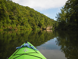 A kayaker eases their way down a quiet section the Current River, one of two rivers that make up the Ozark National Scenic Riverways in Missouri. The Current River is the most spring-fed of all the rivers in the Missouri Ozarks. The river is a favorite with paddlers who enjoy the cold crystal clear water from springs that feed the Current River, including Cave Spring, Pulltite Spring, Round Spring, Blue Spring, and Big Spring. The scenic river is lined with rock ledges, caves, gravel bars and bluffs.<br /> <br /> The Ozark National Scenic Riverways was established in 1964, making it America's first national park area to protect a wild river system. The Ozark National Scenic Riverways, which include the Current and Jacks Fork rivers, is known for its caves, springs, sinkholes and losing streams. Visitors can enjoy water activities, such as floating, canoeing, tubing, swimming, and fishing. Additionally, there are opportunities for hiking, horseback riding, and wildlife viewing. Over 130 miles of waterways and 300 identified caves exist within the park.